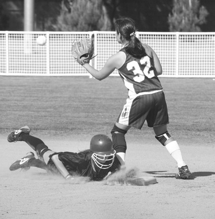 University of La Verne freshman Suzy Riker dives back to second base to beat the tag by Tina Hamayasu (No.32) of Claremont-Mudd-Scripps. La Verne defeated the Athenas, 11-5, Friday at Wheeler Park. CMS came back to beat the Leopards Saturday, 7-6 and 6-5. / photo by Jenna Campbell