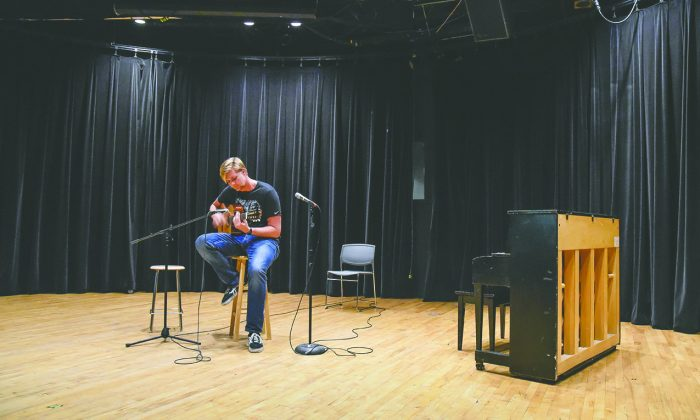 Public administration graduate student Tyler Bennett performs an original acoustic piece, mixing flamenco with his own original riffs Tuesday in the Jane Dibbell Cabaret Theatre. Student Cabaret Productions hosted an open mic night to provide an opportunity for students to perform in front of an encouraging audience without judgement.