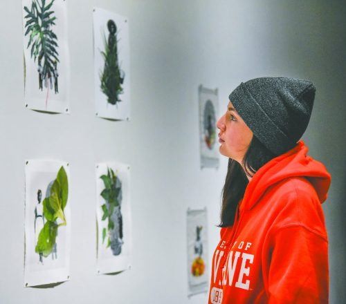 "Freshman communications major Amelia Romo examines Andrea Chung's work at the ""Biomythography"" reception Tuesday in the Harris Gallery. Chung uses materials significant to cultures and the nature of labor within those cultures. / photo by Claudia Ceja"
