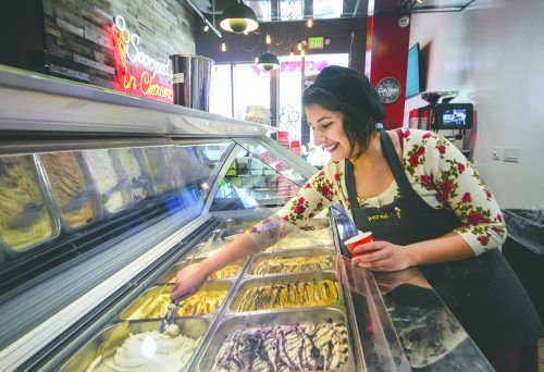 Alicia Rodriguez, ULV alumna and cashier at the Paradis Ice Cream Café in Claremont, scoops up fresh vanilla bean ice cream. The café, which opened in December, features ingredients imported from Denmark. The ice cream is made in the early morning at a product facility in San Fernando and delivered fresh before 11 a.m. daily, when the store opens. / photo by Dorothy Gartsman