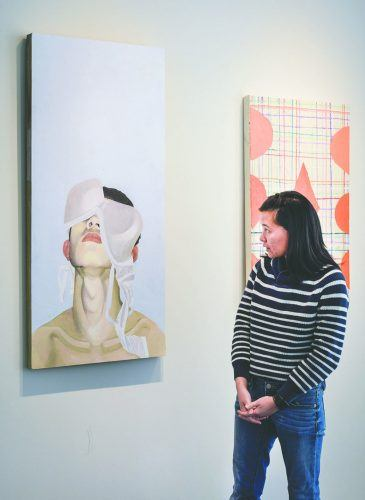 "Damairis Lao, junior art and art history major, stands by her painting ""Branovan 2017"" featured in the exhibition ""Second to Twin"" in the West Gallery in the Campus Center. Lao is one of four students whose pieces are displayed next to the work of Augusto Sandroni, a Southern California artist who is known for abstract paintings. / photo by Sara Flores"