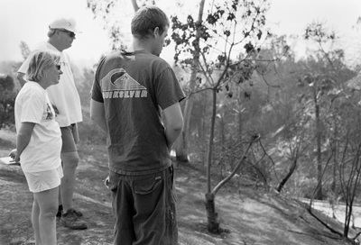 Jane Curl, son Steven and neighbor Mike Stockham stare in amazement at the scorched 40-50 foot ditch situated just to the back of their Claraboya home. The Curls moved into their house around Aug. 1 of this year. For the six-to-seven weeks preceding the fire, they cleared 90 tons of brush from their yard. Their house suffered no damage, although some neighbors were less fortunate. / photo by Adam Omernik