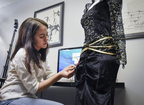 Freshman journalism major Danielle De Luna sews conductive metallic thread into the fabric of an old costume in the Makerspace in Wilson Library. Small details, including the small skull on the dress, were made using the 3D printer, also in the Makerspace. De Luna plans to show her work at the Mini Maker Fair on May 2 in Sneaky Park. / photo by Claudia Ceja