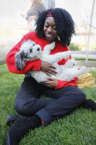 Jasmine Marchbanks-Owens, a graduate student of Master of Arts Social Justice Higher Education Administration program, holds a poodle mix named Crackers, a therapy dog from Paws-to-Share, Tuesday on the University Mall. Crackers' owner, Frank DePalma, said the rescued dog is the first pet he and his wife share. After rescuing Crackers, the DePalmas enrolled in the Paws program. The Office of Housing and Residential Life brings the therapy dogs to mingle with the campus community each month. / photo by Tyler Evains