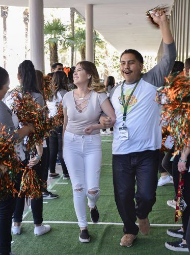 Admitted student Danittza Castro is escorted down the green carpet by Henry Jimenez, senior business administration major, outside the Campus Center during Spotlight Weekend. After their trip down the green carpet, Castro took a photo with La Verne mascots, Leo and Lea.
