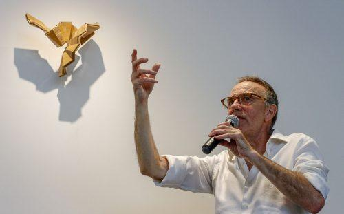"Keith Lord, professor of art, talks about his piece, ""2 Untitled"" made of bamboo flooring, one of seven sculptures in the exhibition, ""Articulation: New Wall Works,"" Wednesday in the West Gallery. Lord said that he finds or is given the materials he uses in his work. He said he cuts wood from frame and crown molding, ceiling beams, lumber and flooring by feel instead of planning the sculpture before its creation. Lord said he once used computer programs to plan his art, but prefers surprises, or ""happy accidents"" while creating. / photo by Tyler Evains"