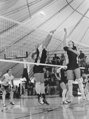 Tricia Schary (No. 21), junior, ULV women's volleyball middle blocker, came up with eight kills against Chapman University on Monday night. Sara Naumann (No. 11), junior, offensive hitter for Chapman, was unsuccessful as ULV swept the Panthers 3-0 (30-21, 30-26, 30-16). / photo by Amy Babin