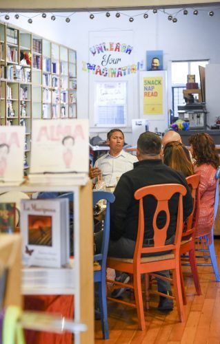Pomona Mayor Tim Sandoval meets with a group of community members at the Café con Libros bookstore Saturday in downtown Pomona to discuss social and community issues. A central topic of discussion was the city's plan for a new homeless shelter and rehabilitation facility. The center will have 400 beds, mental health centers, addiction services and a park for pets.