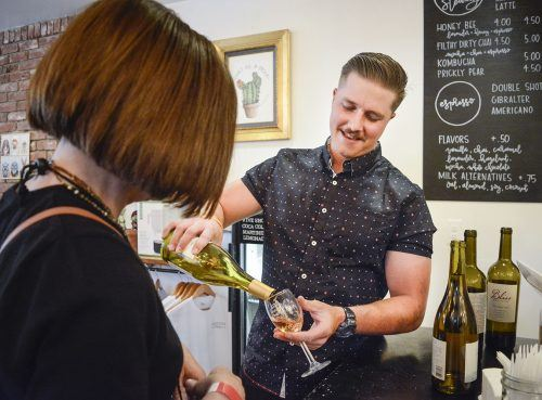 Robert Eddy pours a glass of wine at Cactus Coffee during the Sip of La Verne Wine Walk Saturday. Eddy, whose daily job is an electrician, came to help his girlfriend, Maddy Woods, the manager of Cactus Coffee. Those in attendance at the Wine Walk were given a wine glass and a lanyard filled with tickets to be used at participating businesses serving different varieties of food and wine.