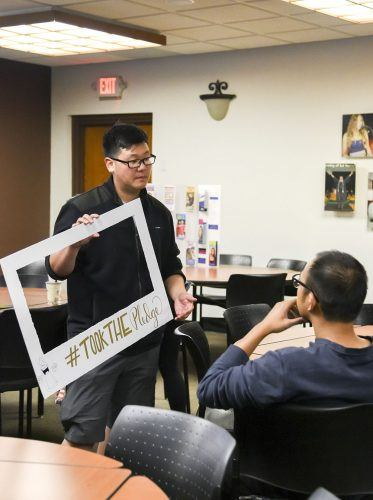 """Jeffrey Chun, junior business administration major; Margaux San Nicolas, junior international business and language major and Isabelle Cheng, senior educational studies major, present their honors senior project on safe sex May 11 in the President's Dining Room. Chun holds their senior project sign """"#TookThePledge"""" for students who take their pledge on putting their bodies first and practicing safe sex. At the end of the semester the students will put the pledge sign photos together to create a final artifact. / photo by Cortney Mace"""