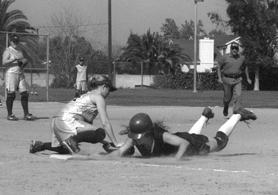 After much deliberation between coaches and umpires, senior shortstop Gina Meza was declared safe at first base. Sophomore Courtney Lum of Whittier defended first base in both games of the doubleheader in La Verne Saturday. La Verne took both games against Whittier, 9-1 and 5-1, after trouncing the Poets 15-0 in Friday's game. ULV is 10-6 on the season. / photo by Jennifer Contreras