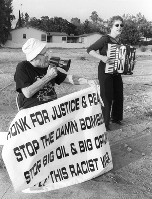 """More than 30 people gathered on the corners of Arrow Highway and Indian Hill Blvd. Friday to encourage people to """"Honk for Peace"""" in opposition to a war with Iraq. Claremont resident Mike Noonan sang along with Marjorie Musser-Mikels of Upland in an improvisational tune entitled """"No blood for oil."""" Musser-Mikels is the Democratic candidate for the House of Representatives in California's 26th Congressional """"Foothill District."""" The two joined members of the community, local churches, including the Claremont Friends Church, and organizations such as the Pomona Peace and Justice Center. The anti-war advocates say they will continue to meet on these corners every Friday from 5 p.m. to 7 p.m. / photo by Jennifer Contreras"""