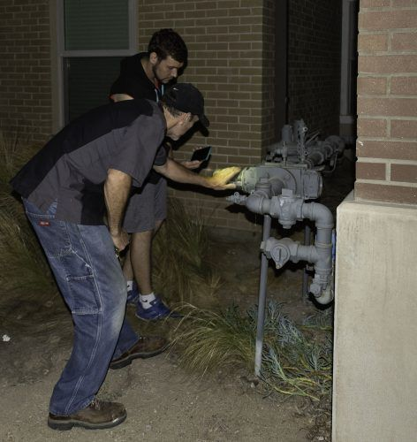 Junior psychology major Curtis Gordon shines his phone flashlight on a gas regulator outside Vista La Verne residence hall for facilities management trade worker Gary Sikes after a 4.4 magnitude earthquake hit La Verne Tuesday at 7:30 p.m. The regulator controls gas that runs through the building to the boilers to provide hot water. / photo by Natasha Brennan