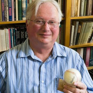 Dr. Stephen Sayles shares one of his favorite mementos, a baseball signed by Negro League ballplayer Buck O'Neil he recieved as a gift from some former students, in a file photo from 2014. Dr. Sayles died Sept. 1 at the age of 73.