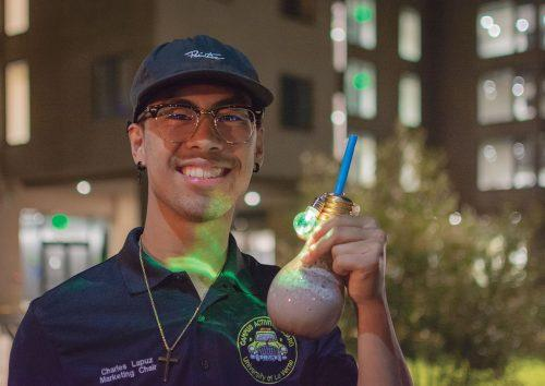 Junior business major Charles Lapuz enjoys the cookies and crème slush from Squidies, at ULV Night Market on Aug. 30. Squidies is the popular 626 Night Market drink vendor that is known for its iconic lightbulb bottles with flashing multi-colored lights attached. Along with the flashy drinks, the Campus Activities Board handed out custom ULV blankets and hosted two food trucks, Mac'D n Loaded and Son of a Bun. Waba Grill was also present at the market and handed out bowls to students.
