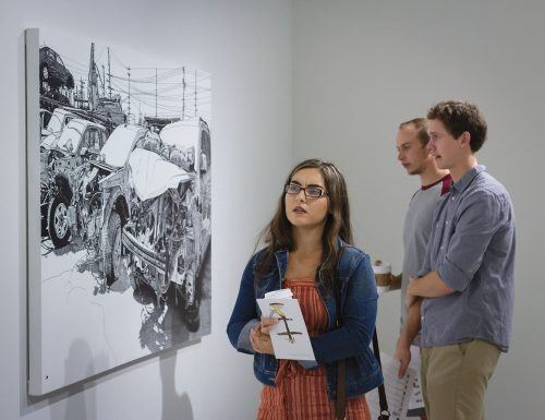 "Senior criminology majors Baily Boschi and Cameron Dice and senior kinesiology major Miles Tsujimoto attend the opening reception of ""Secrets for the Moon"" Tuesday in the Harris Gallery. The exhibit features the work of Ichiro Irie and Lorenzo Hurtado Segovia and runs through Oct. 25. / photo by Melody Blazauskas"