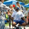 DaeJohn Logan, senior psychology major, squats over a pedestal while students sign his shirt during Club Fair on September 5. He said he wanted to give people a platform to be heard as well as to make people interact during the event. / photo by Kayla Salas