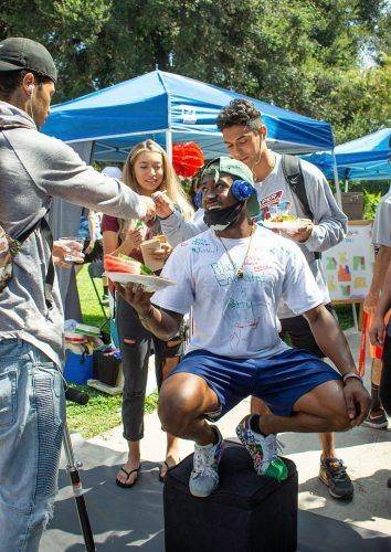 DaeJohn Logan, senior psychology major, squats over a pedestal while students sign his shirt during the club fair Wednesday. He said he wanted to give people a platform to be heard as well as to make people interact during the event. / photo by Kayla Salas