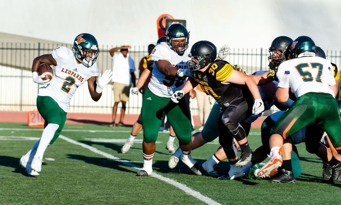 Senior running back Martaveous Holliday runs the ball down field to score a touchdown in Saturday's game against CETYS at Ortmayer Stadium. Senior lineman Toronny Thomas and Freshman linemen William Froman block for Holliday as he gains yardage.