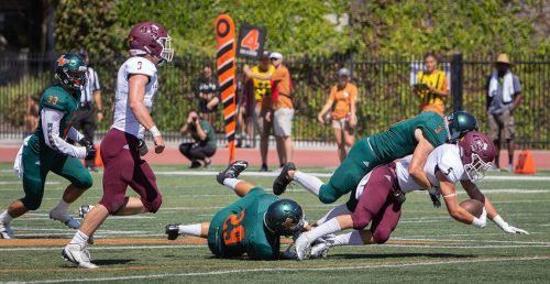 Sophomore linebacker Gabriel Lopez and sophomore cornerback Gary Bojorquez tackle Puget Sound junior wide receiver Michael Zabran on fourth down in the second quarter on Saturday. The Leopards fell to the Loggers at home, 56-28.