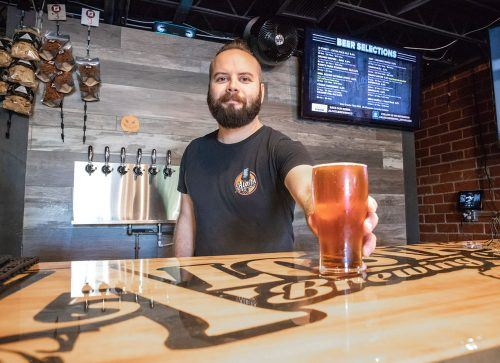 Alosta Brewery employee Iain Irvine shows off a pint of Spadra IPA, one of the brewery's craft beers. Alosta opened last month at 2079 Bonita Ave., its second location. Alosta is open Wednesday through Sunday with different hours each day.