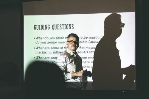 "Assistant Professor of Teacher Education Christian Bracho gives a brief overview of ""Machismo"" or masculinity, and the guiding questions that the panelist were given during the Machismo Panel Event Tuesday in the Campus Center Ballroom. / photo by Jaren Cyrus"