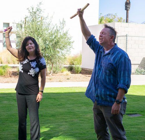 Leticia Arellano, associate professor of psychology, and Trevor Thomson, member of the Karuk tribe, raise their arms to commemorate the Native American women who have died from captivity. Thomson led the ceremonial blessing Monday outside of Citrus Hall with California White Sage. Thomson sang ceremonial songs and blessed the new structure with sage that grows south of the Interfaith Chapel with roughly 20 people present.