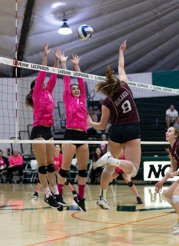 Junior setter Madison Maynes and senior middle blocker Katelyn Winiecki block a spike against Redlands Tuesday night during the pink out game at Frantz Athletic Court. The Leopards beat the Bulldogs, 3-0, while wearing pink jerseys for Breast Cancer Awareness Night.
