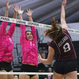 Junior setter Madison Maynes and senior middle blocker Katelyn Winiecki block a spike against Redlands on Tuesday night during the pink out game in the Frantz Athletic Court. The Leopards defeated the Bulldogs 3-0. La Verne's next match is Saturday against Occidental.