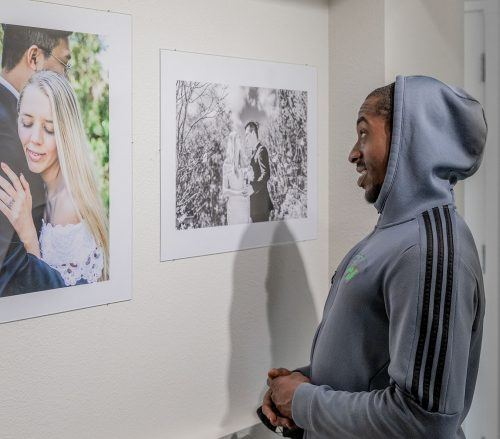 "Senior psychology major Dae'John Logan views the ""Weddings Through the Lens"" exhibit Wednesday in the Ground Floor Gallery in Miller Hall. The exhibit, featuring student work from the Wedding and Events photography class, was curated by senior photography major Celeste Drake. The ""Weddings Through the Lens"" exhibit runs through Nov. 5. / photo by Jaren Cyrus"