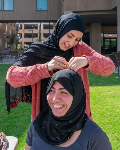 Nala Kachour, president of the Muslim Students' Association, pins a hijab on Pomona Salcido, senior mathematics major, Monday in the Citrus Courtyard. For Islam Awareness Week, Kachour explained the purpose of the traditional head scarf. Kachour encouraged people to wear the hijab around campus and note the reaction they receive from others.