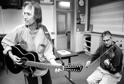 """A small group of University of La Verne students gathered in Founders Hall 22 for a lecture and performance by former Byrds band member John York. York played the famous '60s song """"Turn, Turn, Turn"""" with music professor David Brock (left) Monday night. / photo by Liz Lucsko"""