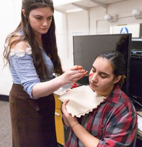 Jordan Nelson, junior theater major, applies makeup to look like a scar on freshman music major Danielle Hernandez for the haunted house Tuesday night in Dailey Theatre. She gets the actors ready for the haunted house by applying special effects makeup to make each character look as real and scary as possible.