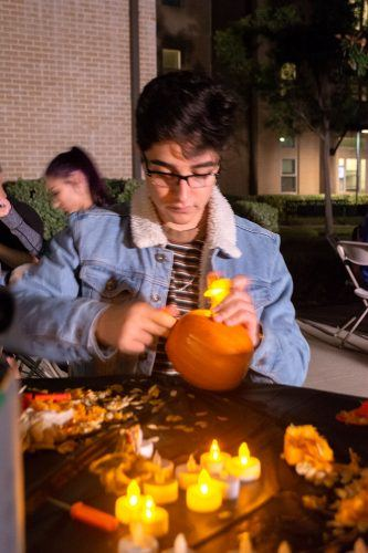 Freshman business administration major Eric Esquivel works diligently on carving a pumpkin Oct. 24 outside the Hanawalt House at the Campus Activity Board's Hallowfest. / photo Veronyca Norcia