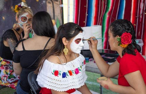 Jahna Rae Aieto paints Raquel Arenas' face Saturday for En Memoria, the Fairplex's second annual Dia De Los Muertos Celebration. The event included live music, food vendors, art and a low rider car show. / photo by Melody Blazauskas