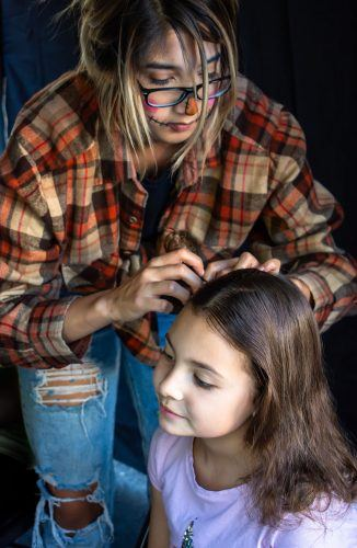 Isabella Rojas, 7, gets her hair braided by Toni Arevalo of Kut Haus Salon Saturday afternoon at the 37th Annual Village Venture in Claremont. The event included a costume contest and parade, pumpkin carving, booths featuring local businesses and a beer, wine and cider garden. / photo by Natasha Brennan
