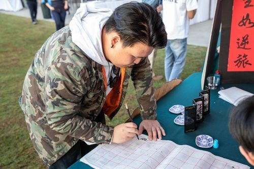 Senior psychology major Xingda Zhu writes Chinese characters at the Chinese booth at the International Education Festival Nov. 15. The festival, hosted by the Office of International Services and Engagement, encouraged students to learn about different cultures. / photo by Jaren Cyrus