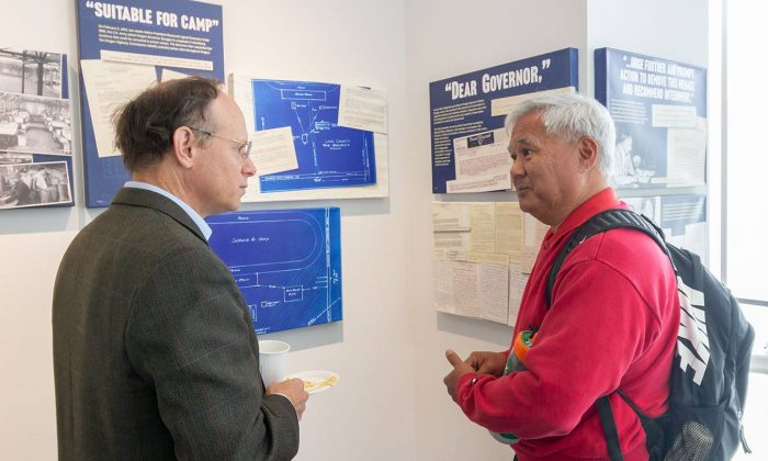 "Professor of Kinesiology Paul Alvarez shares with Kenneth Marcus, professor of history, his personal stories connected with the ""Architecture of Internment"" exhibit at a reception for the exhibit Tuesday in the Campus Center. Members of Alvarez' family were incarcerated in the Japanese internment camps in the 1940s. The exhibit runs through Feb. 28 in the West Gallery."