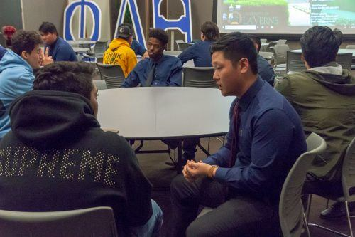 Jeffrey Chun, senior business administration major, talks with a prospective student about the Phi Delta Theta experience in the Campus Center Ballroom during Wing Night Tuesday. He discussed the fraternit's philanthropy and said being in this frat changed his college experience. Wing Night is a fraternity recruitment event. / photo by Nikky Huynh