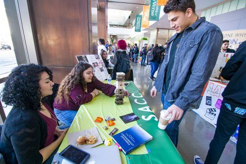 Sociology, Anthropology, Criminology Club club secretary, Siboney Ioppolo, and club president, Miriam Rangel, play a game of Jenga with senior criminology student Caleb Johnson at the Club Fair on Feb. 6. Free food was available to all students at the event. / photo by Molly Garry