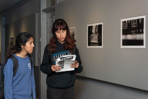 "Edith Oceana and Kristin Reed, both freshman broadcast majors, find the captions to each photo in the exhibit ""Return: The Landscape of Memory,"" by photographer Sylvia de Swaan, Thursday in the Carlson Gallery in the basement of Miller Hall. The exhibit includes an array of self portraits in which de Swan holds antique photographs of family members and photographs from her childhood. / photo by Katelyn Keeling"