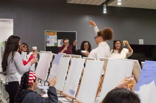 """Melissa Moss, far right, leads a non-alcoholic toast to celebrate womanhood and self-care at the """"Essence of a Womyn"""" event hosted by social justice in higher education administration graduate students in the Citrus Hall main lounge March 6. / photo by Jaysin Brandt"""