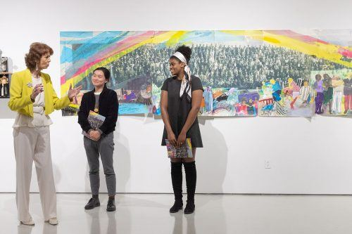 """Artist Phoebe Beasley, Damairis Lao senior art and art history major and Shyonta Glothon sophomore psychology and theatre major discuss their collaborative efforts to create a painting titled """"Class of '33,"""" at the """"Unsung Requiem: Lost then Found"""" exhibition April 4 in the Harris Gallery. / photo by Kayla Salas"""