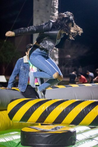 Sophomore educational studies major Xochilt Aviles bounces in the Meltdown inflatable during Astroverne April 18 at Campus West. The event, which was themed after rapper Travis Scott's 2018-19 world tour, Astroworld, featured live music, food trucks, carnival games and prizes. / photo by Ariel Torres