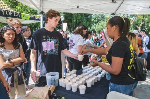 Freshman communications major Alex Pignataro receives wildflower seeds from Stephanie Joseph, sophomore communications major, at the Campus Activities Board booth at the Earth Day Fair in Sneaky Park Wednesday. Other clubs also had their own booths. / photo by Molly Garry