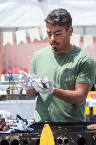 Gabriel Salazar of San Bernardino makes a Baja-style bacon wrapped hotdog Saturday at the Upland Lemon Festival. The event also featured live bands, various vendors and carnival-style games. / photo by Ariel Torres