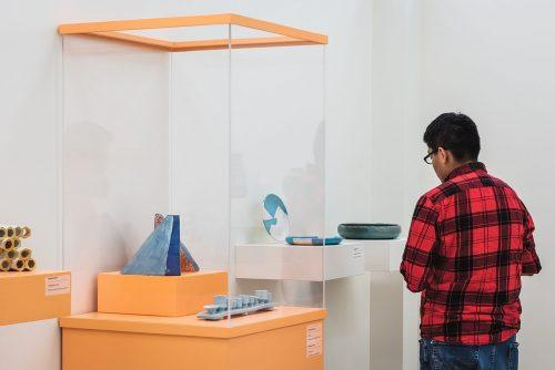 "Sonny Acosta studies ""Set of Geometric Plates"" by Max Alvarez, a student of Flintridge Prep in La Cañada-Flintridge, Sunday at the American Museum of Ceramic Art in Pomona. The piece is part of the 2019 SoCal High School Ceramics Exhibition. / photo by Katelyn Keeling"