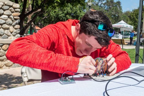 Sophomore computer science major Joseph Mueller puts the final touches on his police siren project Wednesday at the Mini Maker Fair in Sneaky Park. It has four light patterns that change as wires are moved into different connectors. / photo by Katelyn Keeling