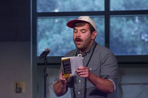 """Sam Sax, a poet from Oakland, California, reads from his book, """"Madness."""" The poetry from his debut collection focuses on queer sexuality, addiction and mental health. The event, """"A Night of Poetry,"""" was held May 9 in the Edmunds Ballroom at Pomona College. / photo by Kayla Salas"""