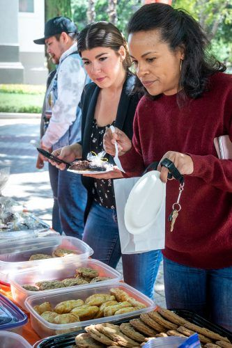 Lisa Lester, associate director for housing operations, and Susie Haynes, assignments coordinator for housing and residential life, consider their options at a bake sale Monday in the Johnson Family Plaza. All the money raised was for Andrew Tompkins, a former member of the swim and dive team, who after beating cancer in 2018, learned the cancer had returned. / photo by Nikky Huynh